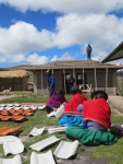 During a minga, community members paint tiles for the new school bathroom